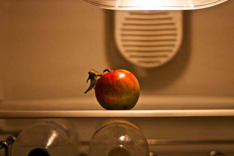Close-up of apple on shelf in refrigerator