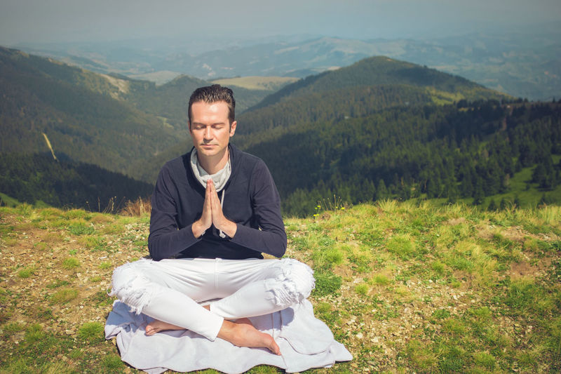Full length of man practicing yoga on mountain