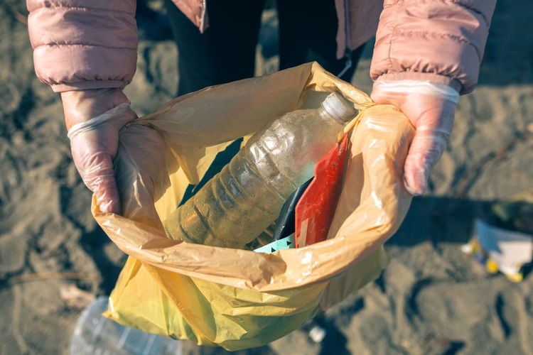Midsection of woman showing plastic with garbage