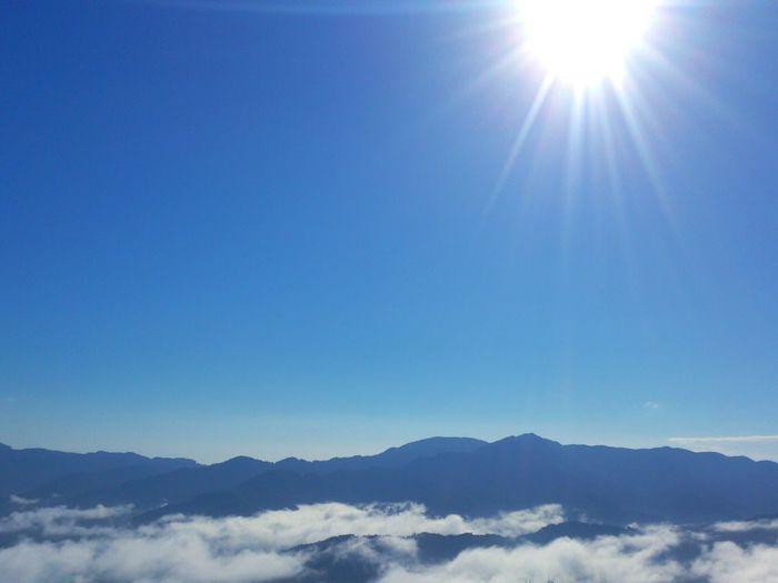 Sun shining through clouds over mountains