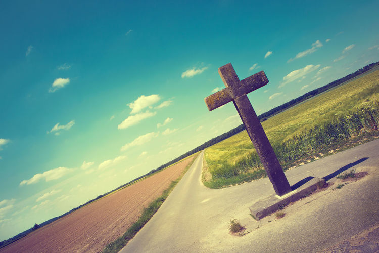 Christian Cross Christianity Clouds And Sky Copy Space Country Road Cross Crossroads Farmers Land Fields And Sky Journey Landscape No People Oblique Perspektive Outdoors Pastel Colors Positive Vibes Religion Rural Scene Stone Cross The Way Forward Tranquil Scene Vanishing Point Warm Day