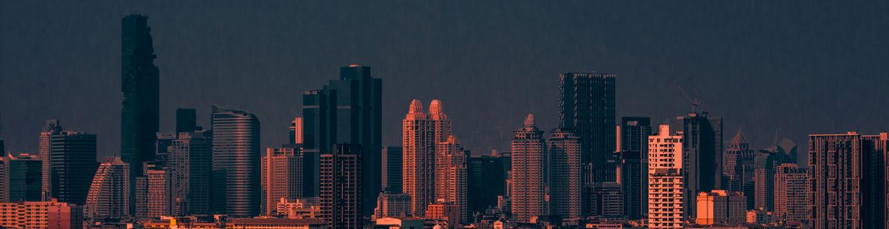 Modern buildings in city against sky at night