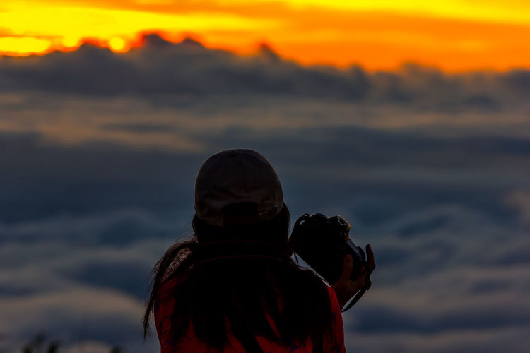 Rear view of woman with camera against cloudscape during sunset