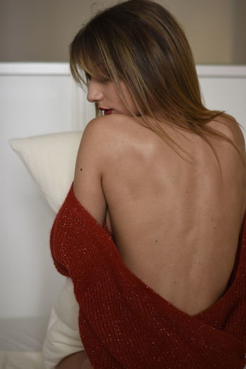 Rear view of sensuous young woman sitting at home