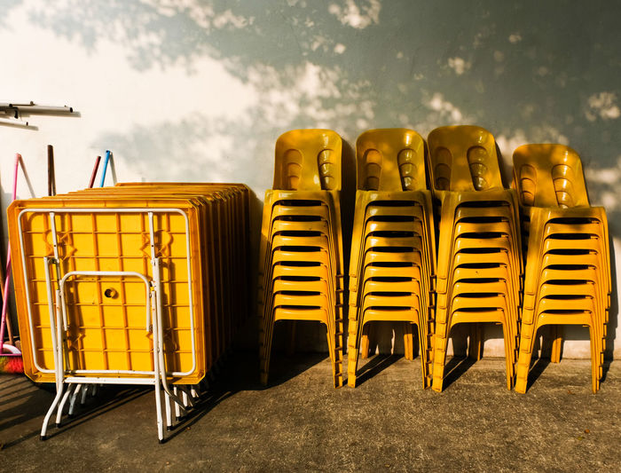 Stacked Yellow Chairs Against Wall
