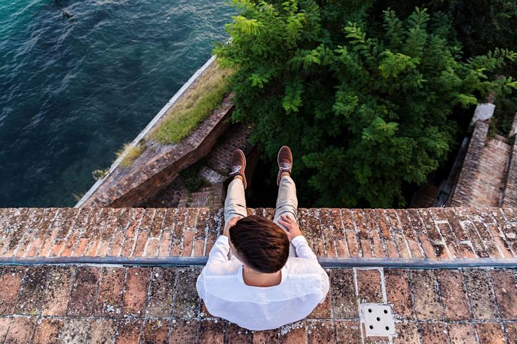 High angle view of man sitting by sea