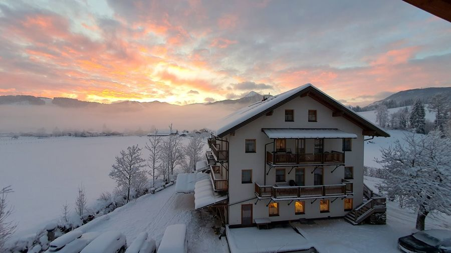 Snow covered houses by building against sky during sunset