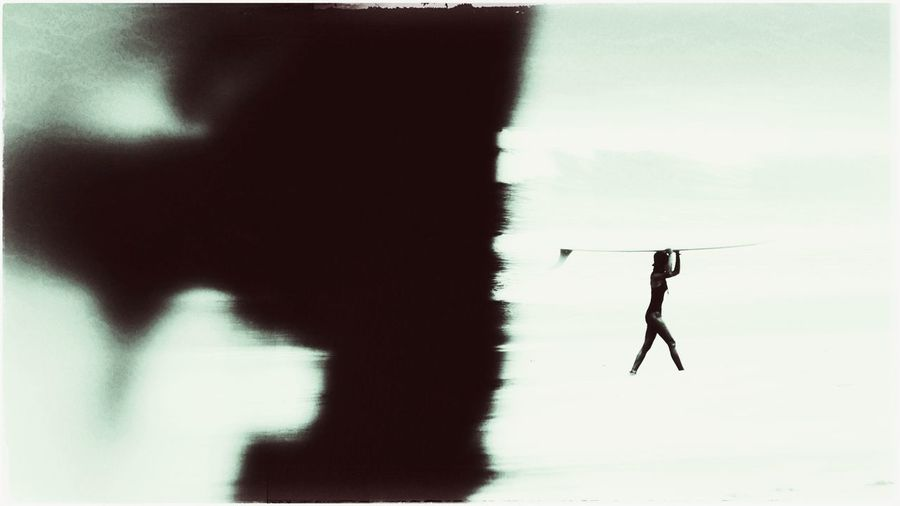 Silhouette person standing in water against sky