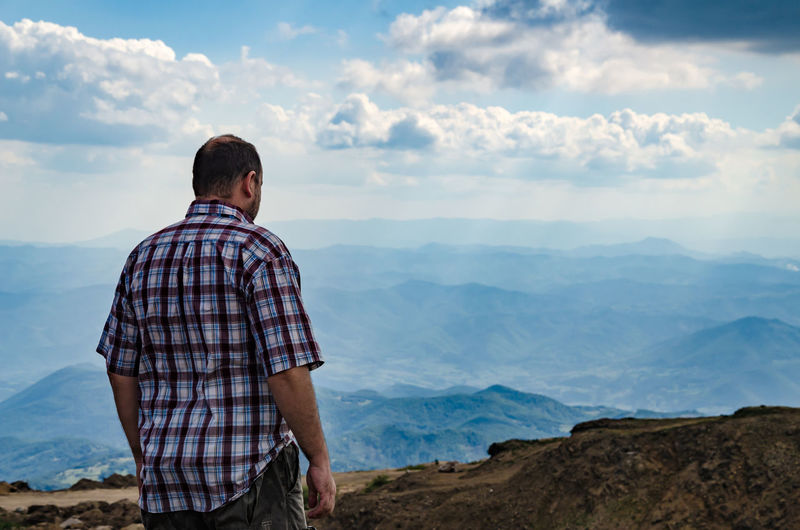 Man dressed for hiking observing a landscape from top of kopaonik mountain, serbia
