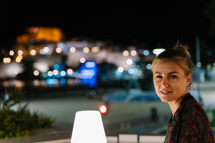 Portrait of woman against illuminated city at night