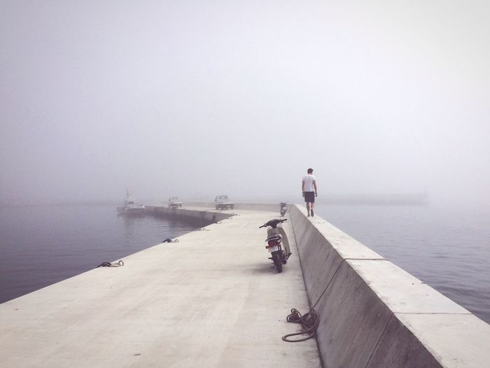 Rear view of man walking on retaining wall at pier in sea during foggy weather