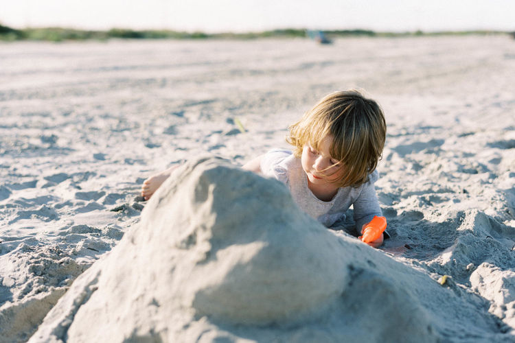 Rear view of boy on rock at beach