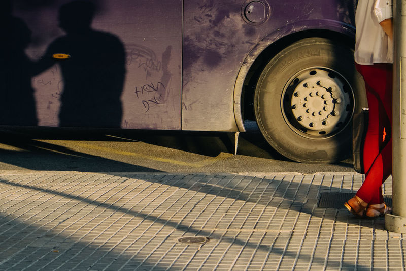 Low Section Of Woman Standing On Sidewalk By Bus