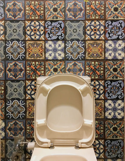 Toilet bowl against tiled wall