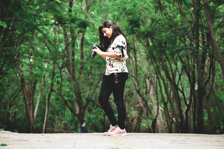 Side view of woman holding camera while standing on road against trees