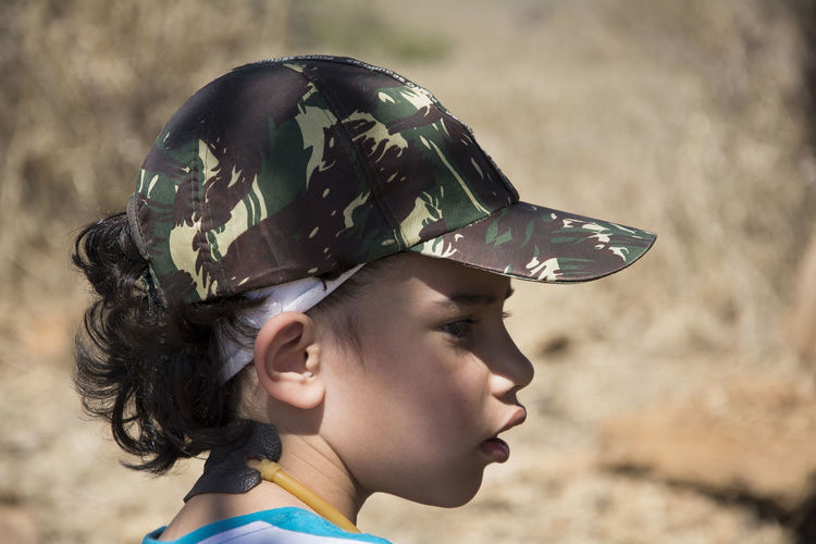 Close-Up Of Boy Wearing Camouflage Cap On Field