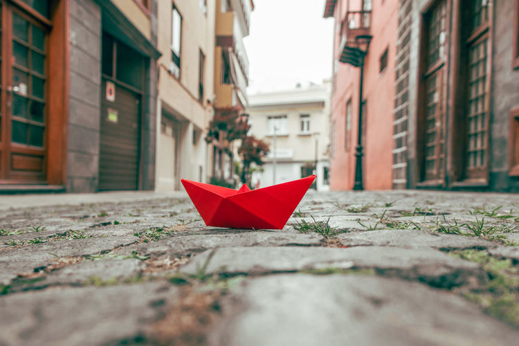 Close-up of paper boat on street amidst building