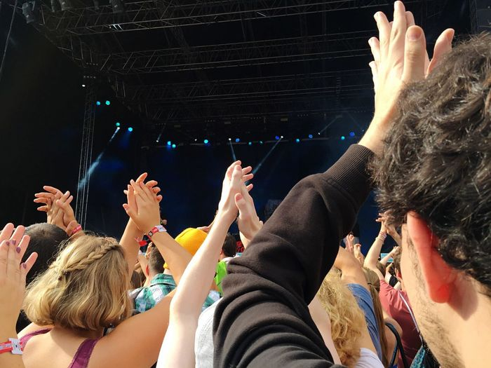 Rear view of audience applauding at music concert