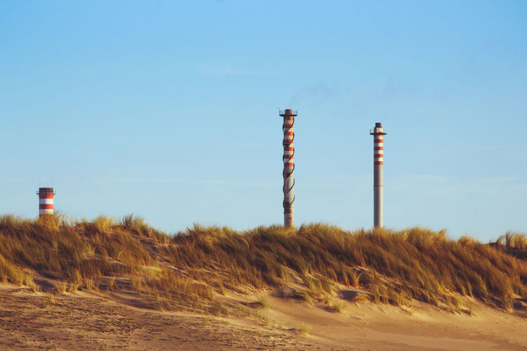 Chimneys of a factory behind some sand dunes