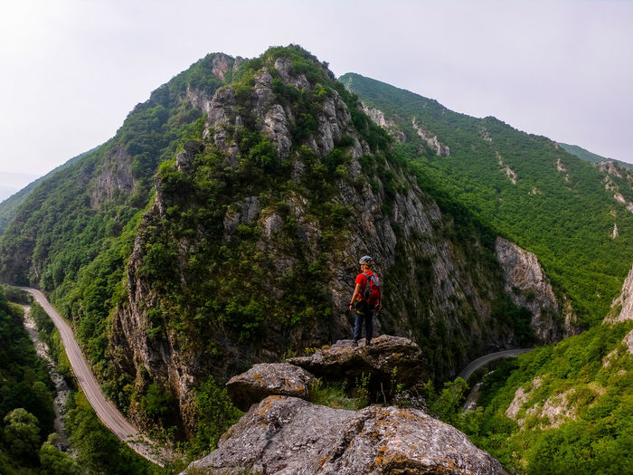 Man on rock by mountain against sky