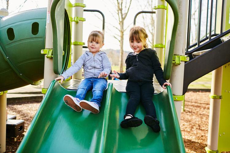 Siblings sitting on swing at park