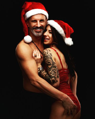 Young smiling couple wearing santa's hats and hugging on black background
