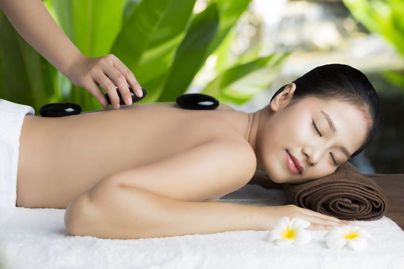Cropped hand putting stones on woman back at spa