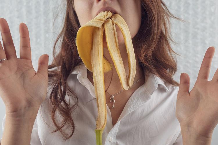 Midsection Of Woman Eating Banana Peel