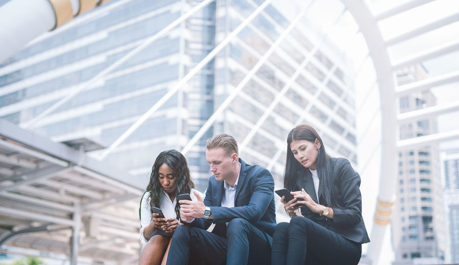 Business colleagues using smart phone while sitting against buildings in city