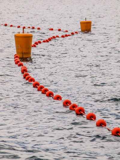 Water No People Buoy In A Row Floating Red Orange Color Floating On Water Close-up Sea Day Nature Outdoors Beauty In Nature Safety Tranquility Group Of Objects Rippled