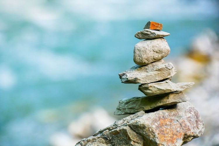 Close-up of stone stack on rock against sea