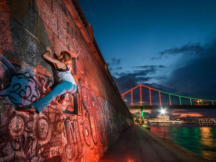Midsection of woman at illuminated bridge against sky