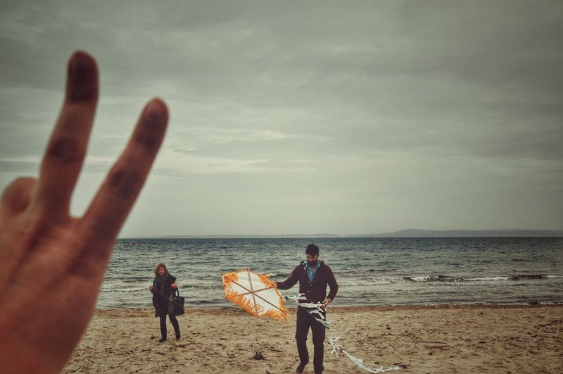Cropped Hand Showing Peace Sign Against Man With Kite At Beach Against Cloudy Sky