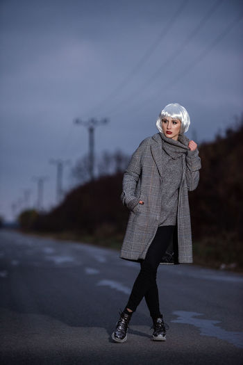 Full length portrait of woman standing on road during winter