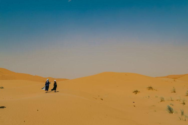 People in desert against sky
