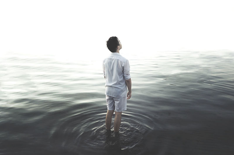 Rear view of man standing in water