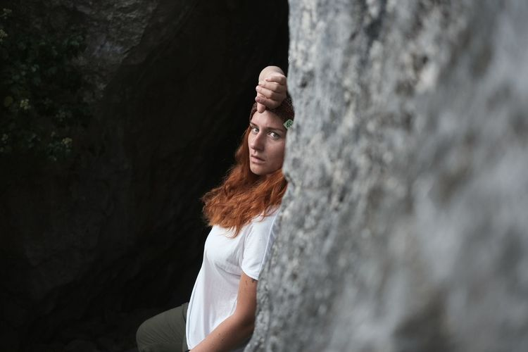 Portrait of young woman looking away while standing against wall