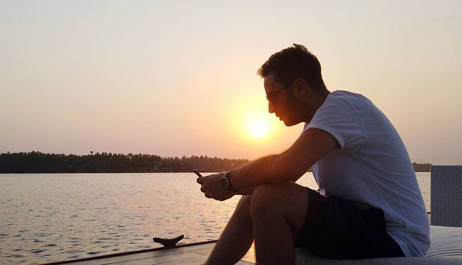 Side view of man using smart phone while sitting against sky during sunset