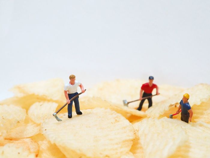 Close-up of figurines on potato chips against white background