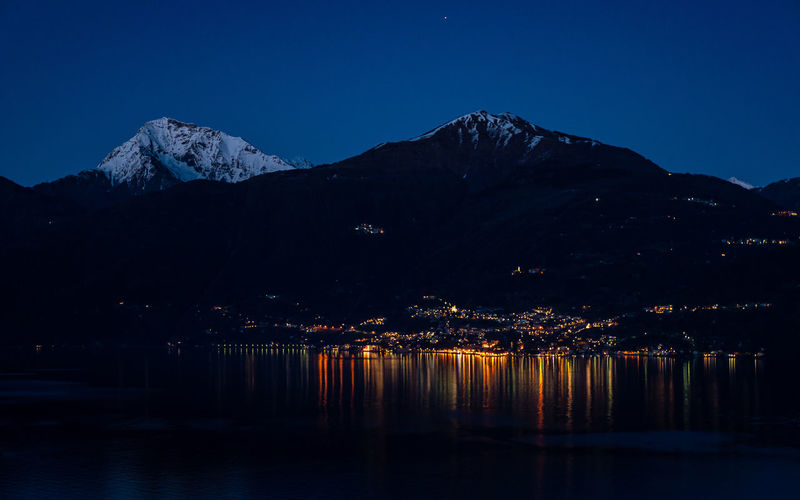 Scenic view of lake by snowcapped mountains against clear sky at night