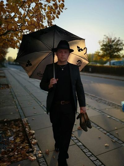 Portrait of young man holding umbrella standing on rainy day