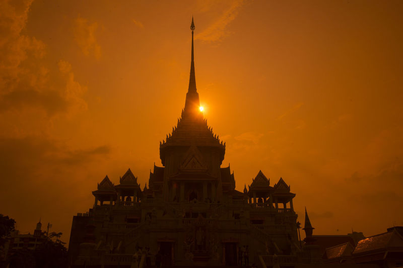 Low angle view of buddhist temple against orange sky