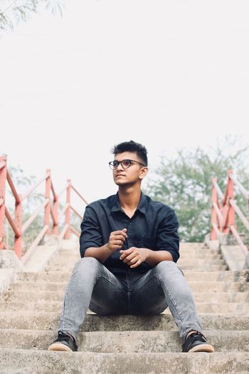 EyeEm Selects Sunglasses Sitting Black Hair Young Adult Front View Fashion Stories Focus On Foreground One Person People Outdoors Cool Attitude Young Men Adult Day Adults Only Only Men One Man Only One Young Man Only Sky Portrait
