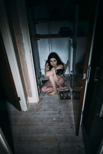 Portrait of woman sitting on door at home