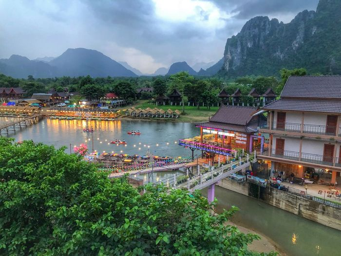 Scenic view of lake by buildings against mountains