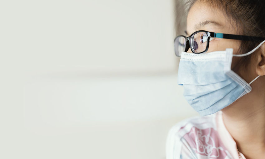 Close-up of girl wearing mask looking away sitting at home