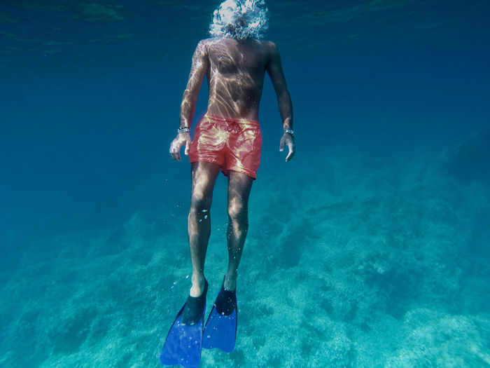 Rear view of man swimming in sea