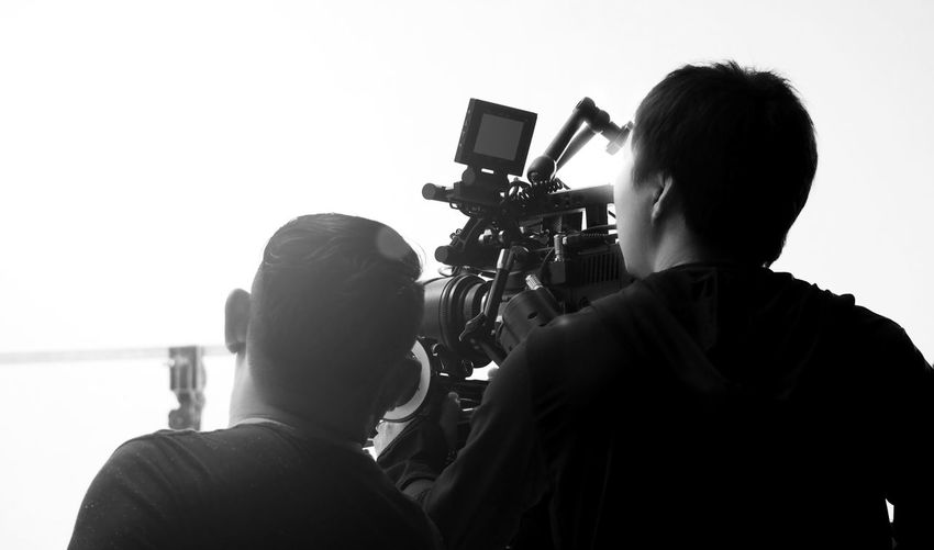 Rear view of operators using camera in studio