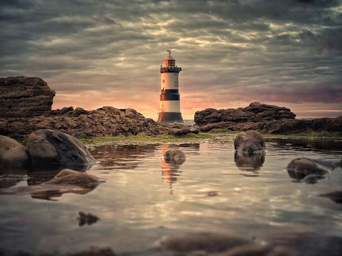 Reflection of lighthouse in water on rock against sky