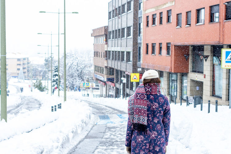 Rear view of woman walking on snow covered street in city